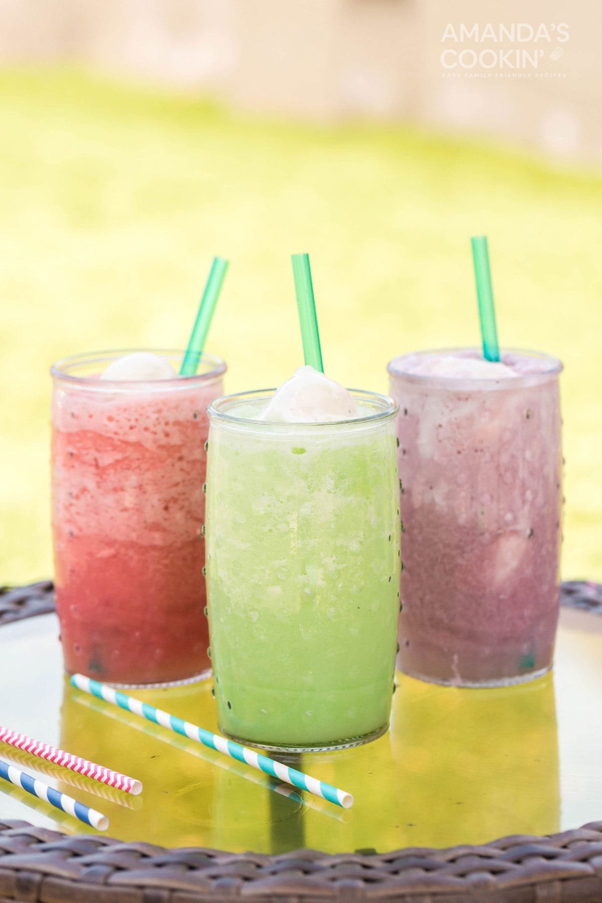 three different colored slushie floats on a table outside
