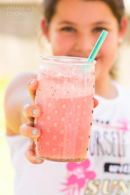 girl holding glass of pink slushie