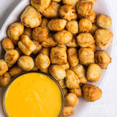 overhead view of pretzel bites on a plate with cheese sauce