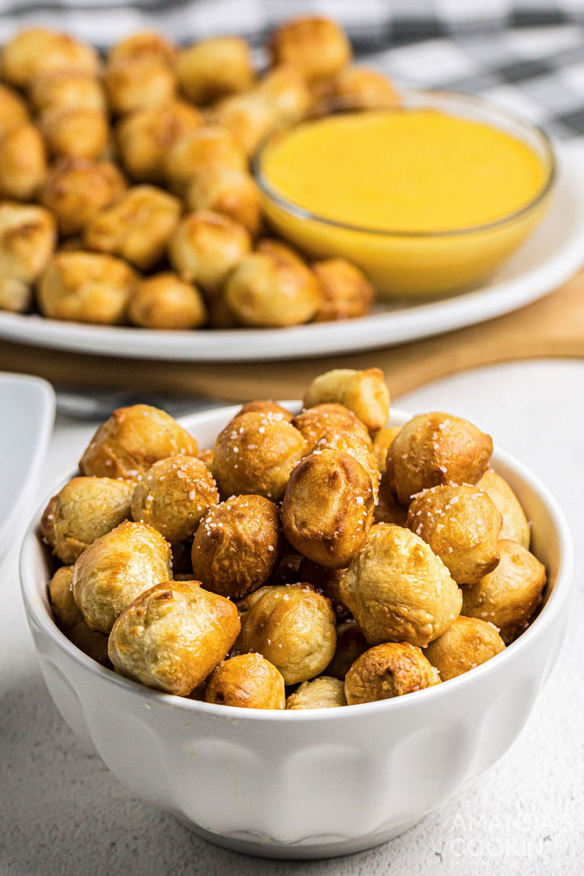 bowl of pretzel bites with cheese in the background