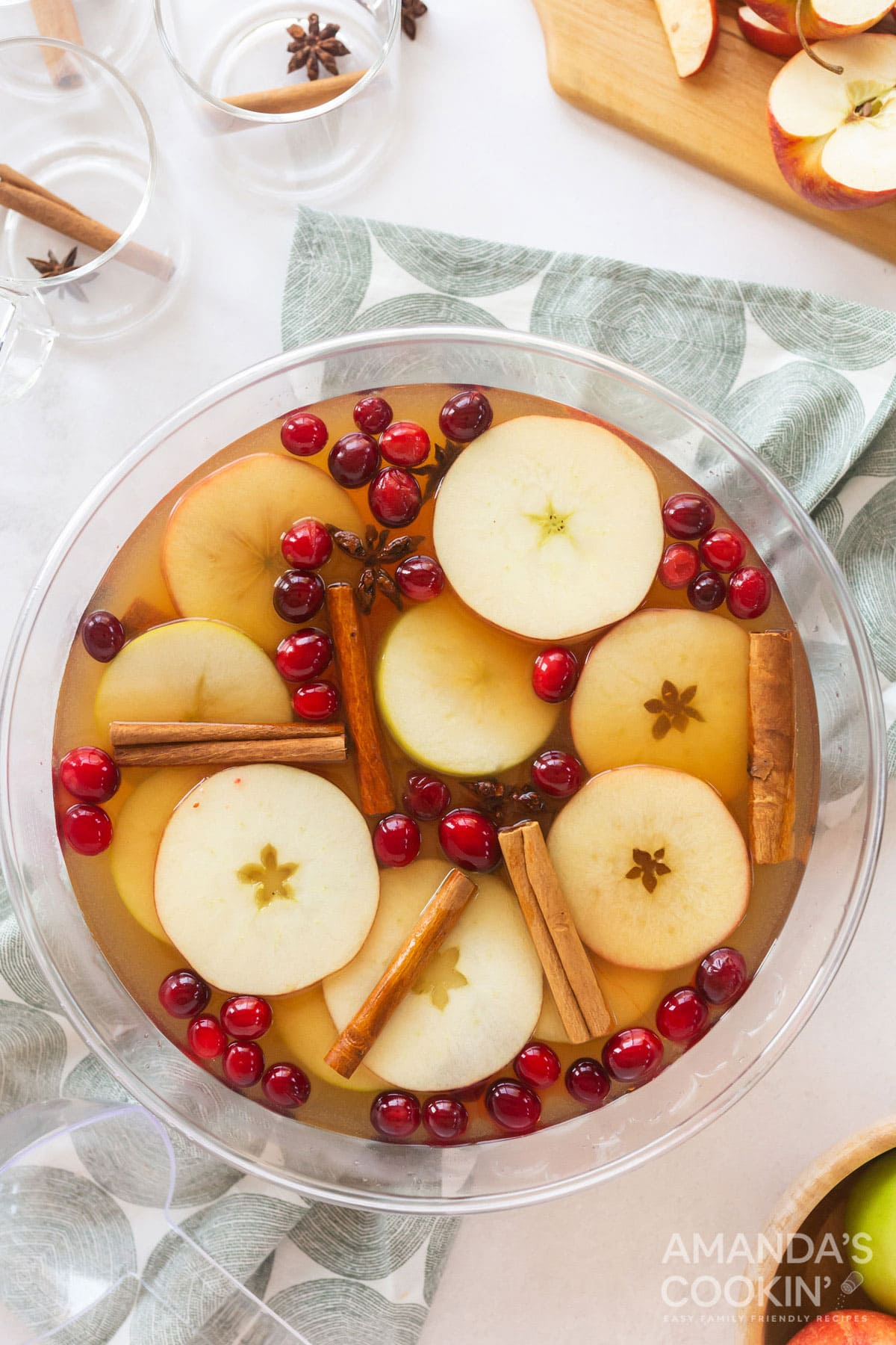 overhead view of a punch bowl filled with hot apple cider and garnished with apple slices