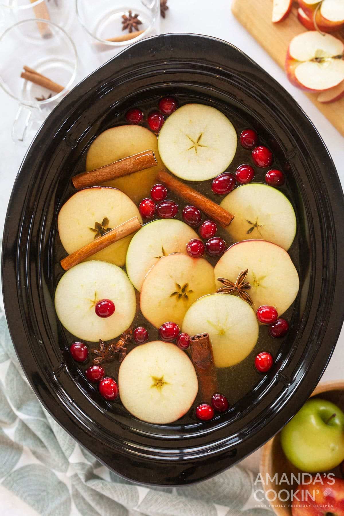 hot apple cider with garnishes in a crockpot