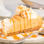 slice of no bake pumpkin cheesecake on a plate drizzled with caramel