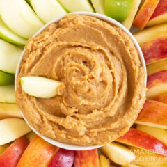 cowl of peanut butter apple dip surrounded by apples