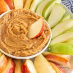 bowl of peanut butter dip surrounded by apple slices