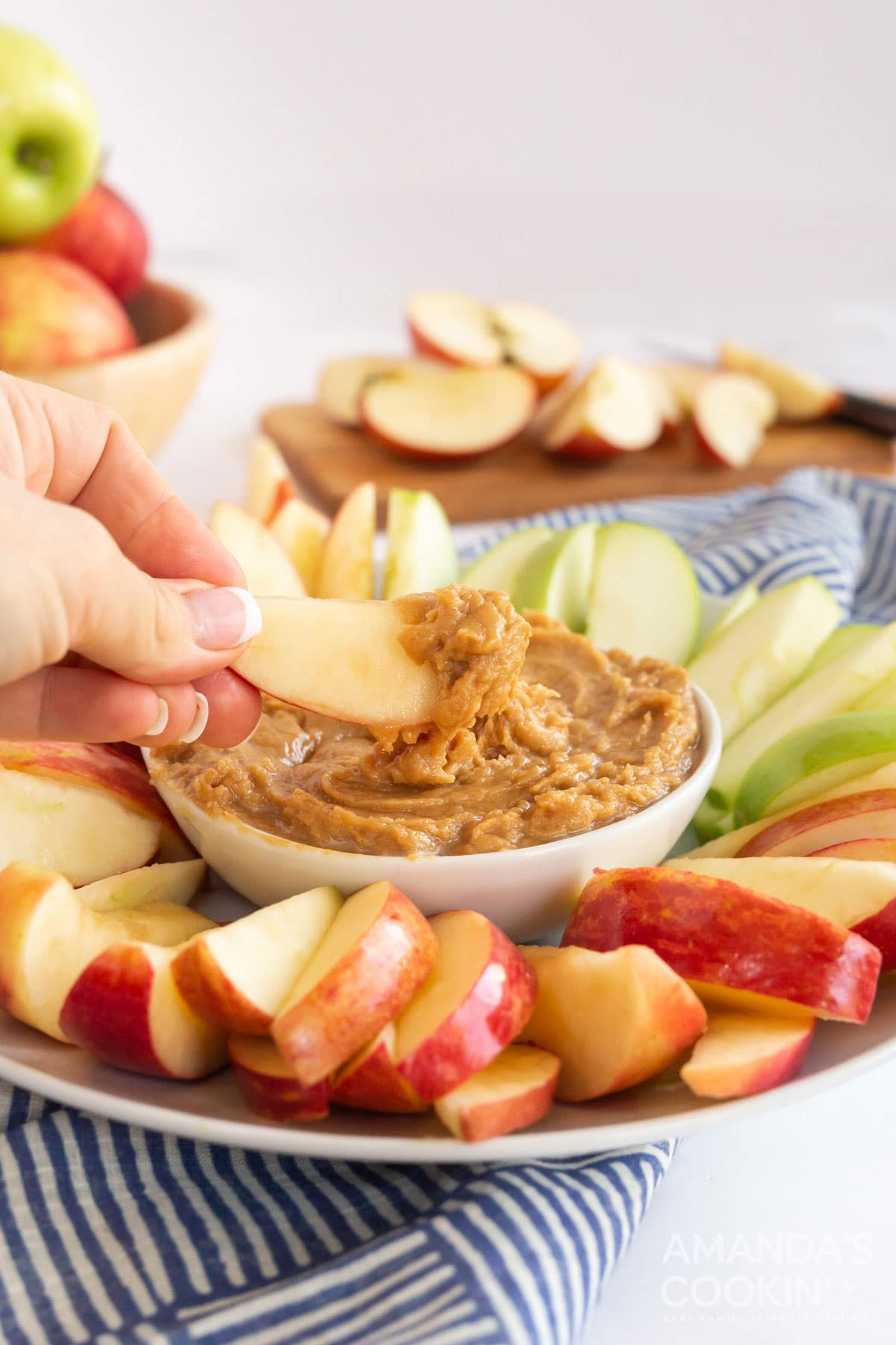 person dipping apple slice in peanut butter apple dip