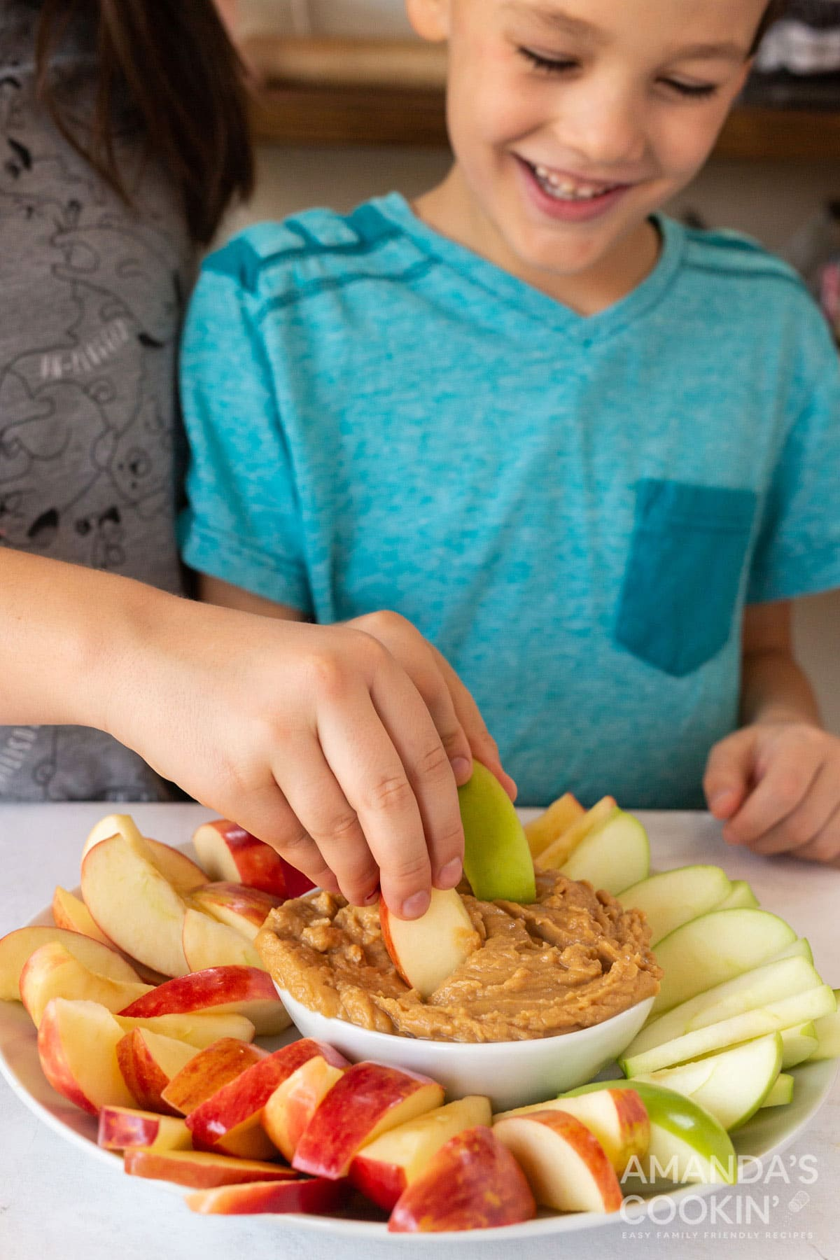 kids dipping apple slices into peanut butter fruit dip