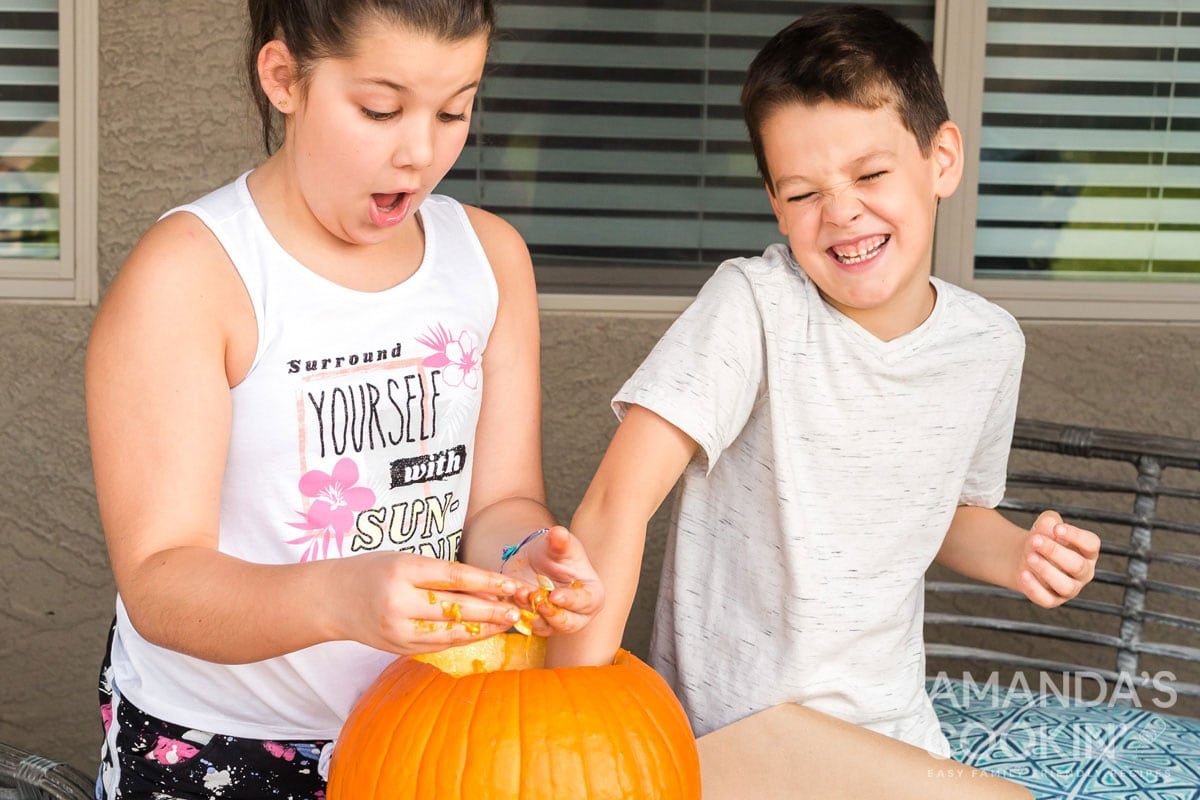 kids cleaning out a pumpkin