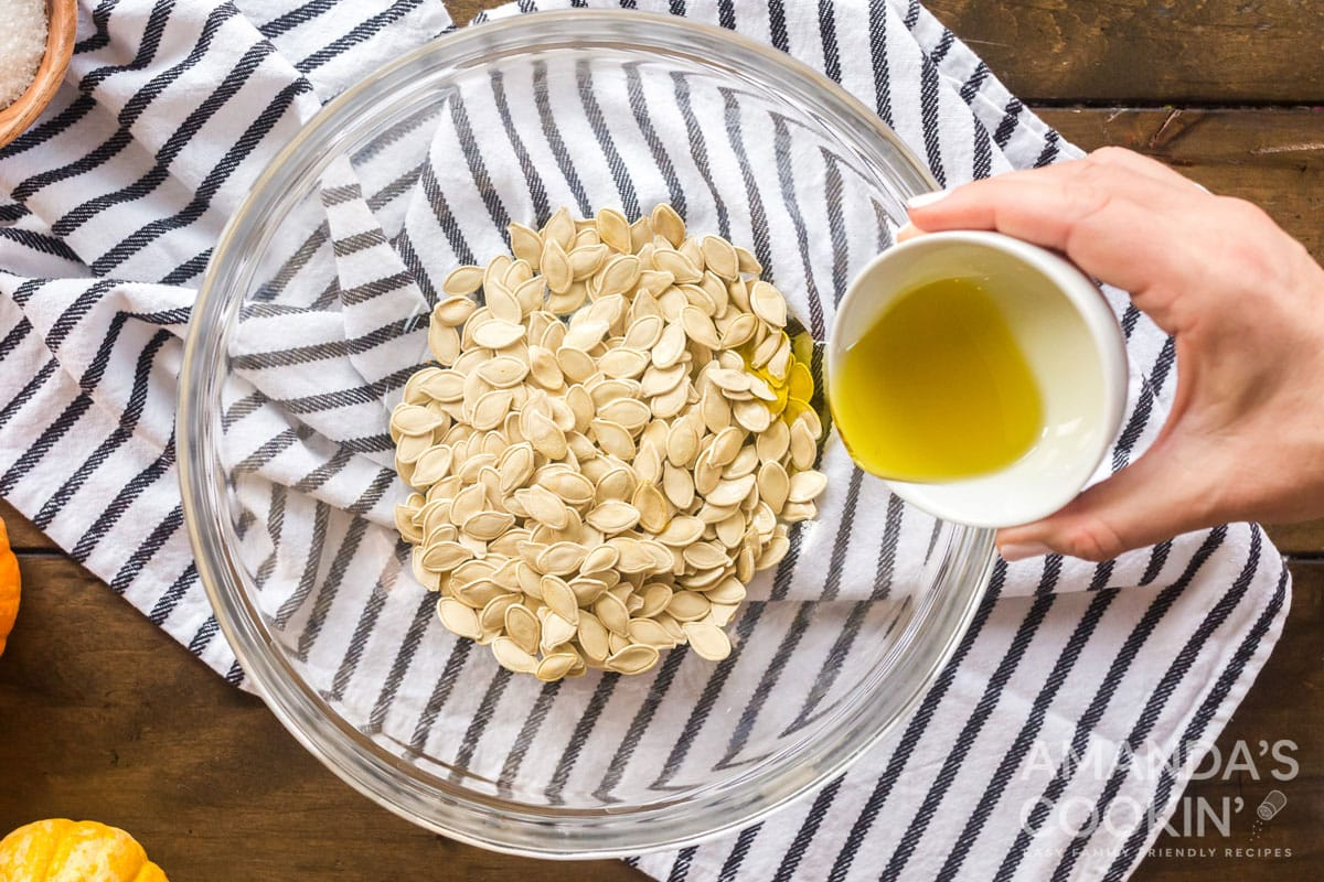 adding olive oil to pumpkin seeds in bowl