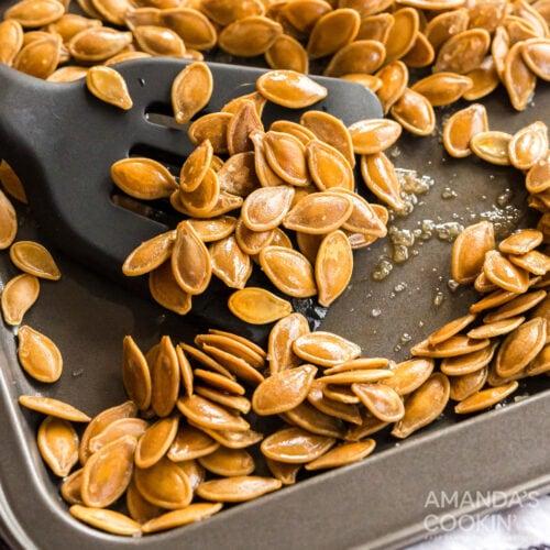 cookie sheet of roasted pumpkin seeds and spatula