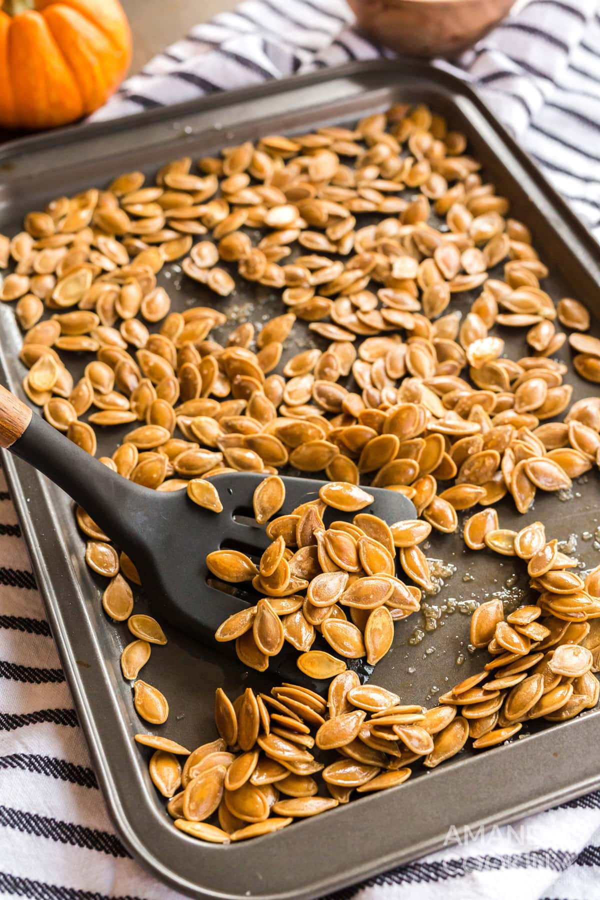 cookie sheet of roasted pumpkin seeds with a spatula