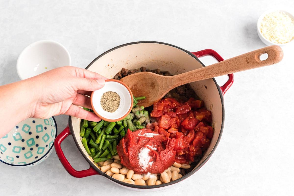 adding seasoning to pot