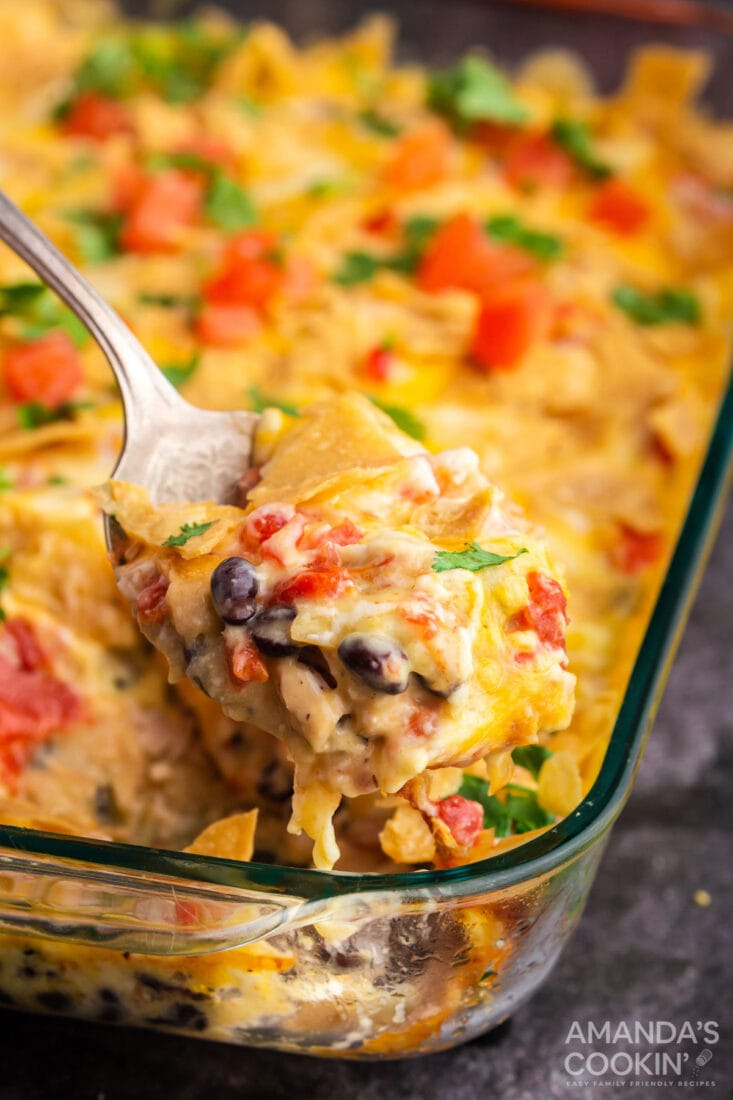 spoon lifting out a serving of mexican chicken casserole