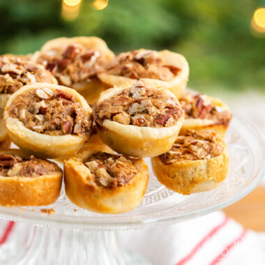 pecan tassies piled on a cake plate