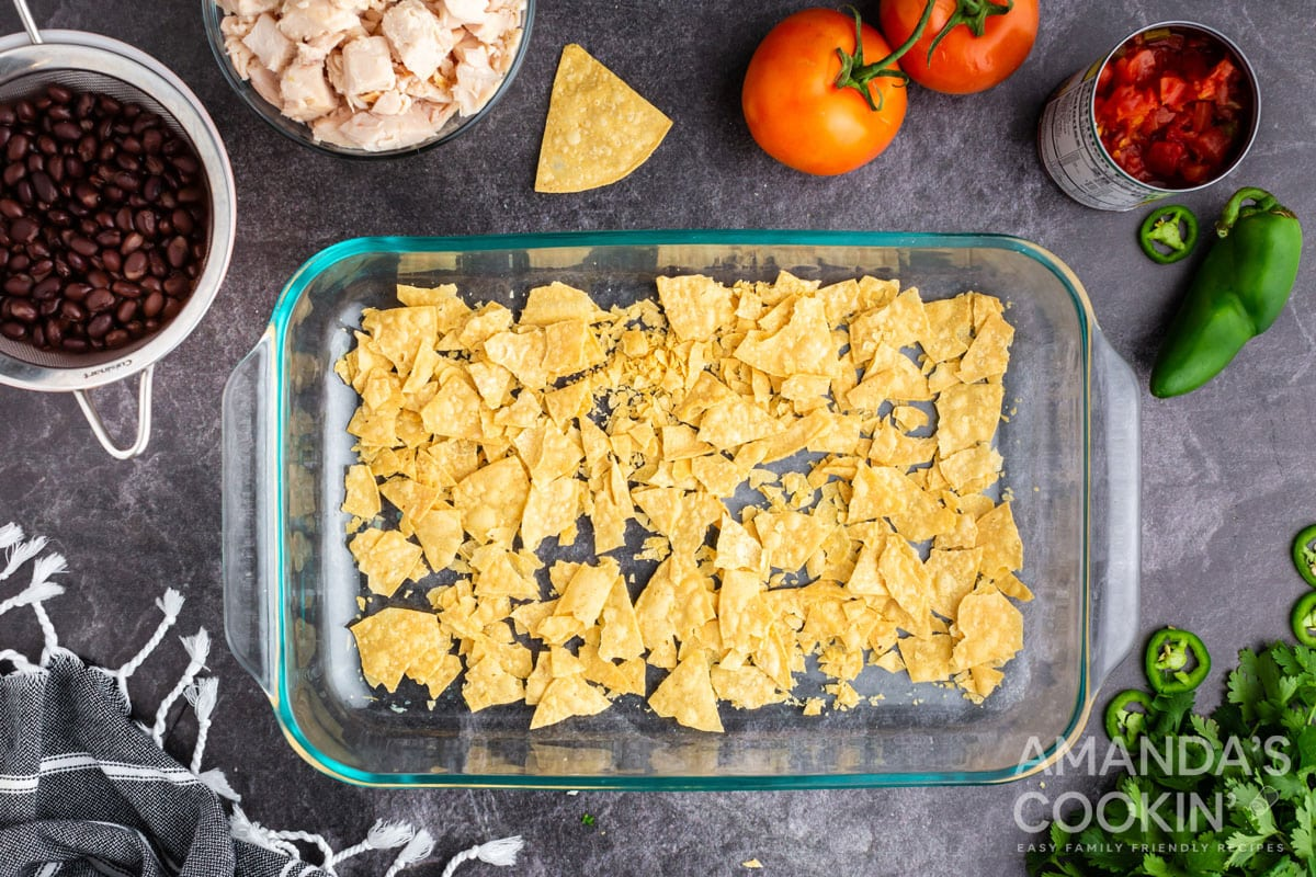 crushed tortilla chips in bottom of casserole dish