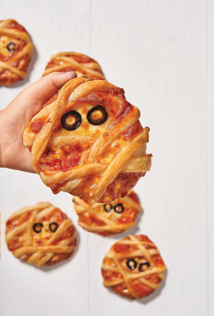 child holding mini mummy pizza
