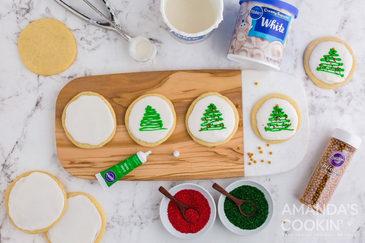 adding christmas trees with decorator gel on iced cookies