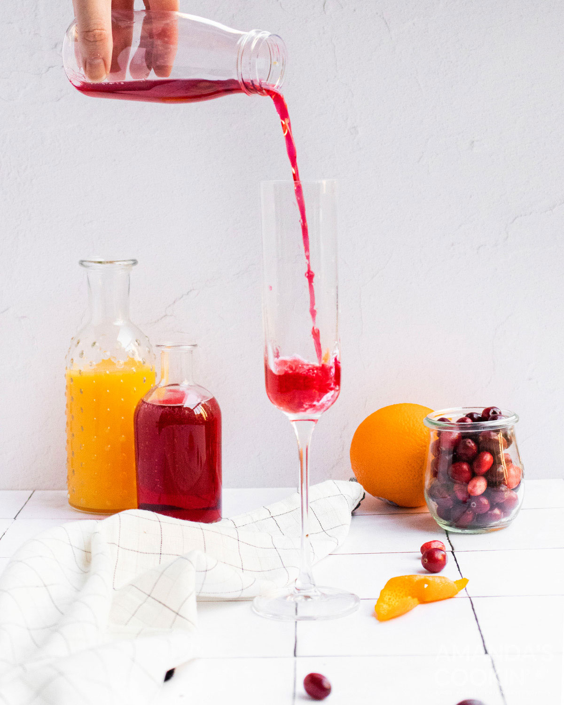 pouring cranberry juice into a chamagne flute