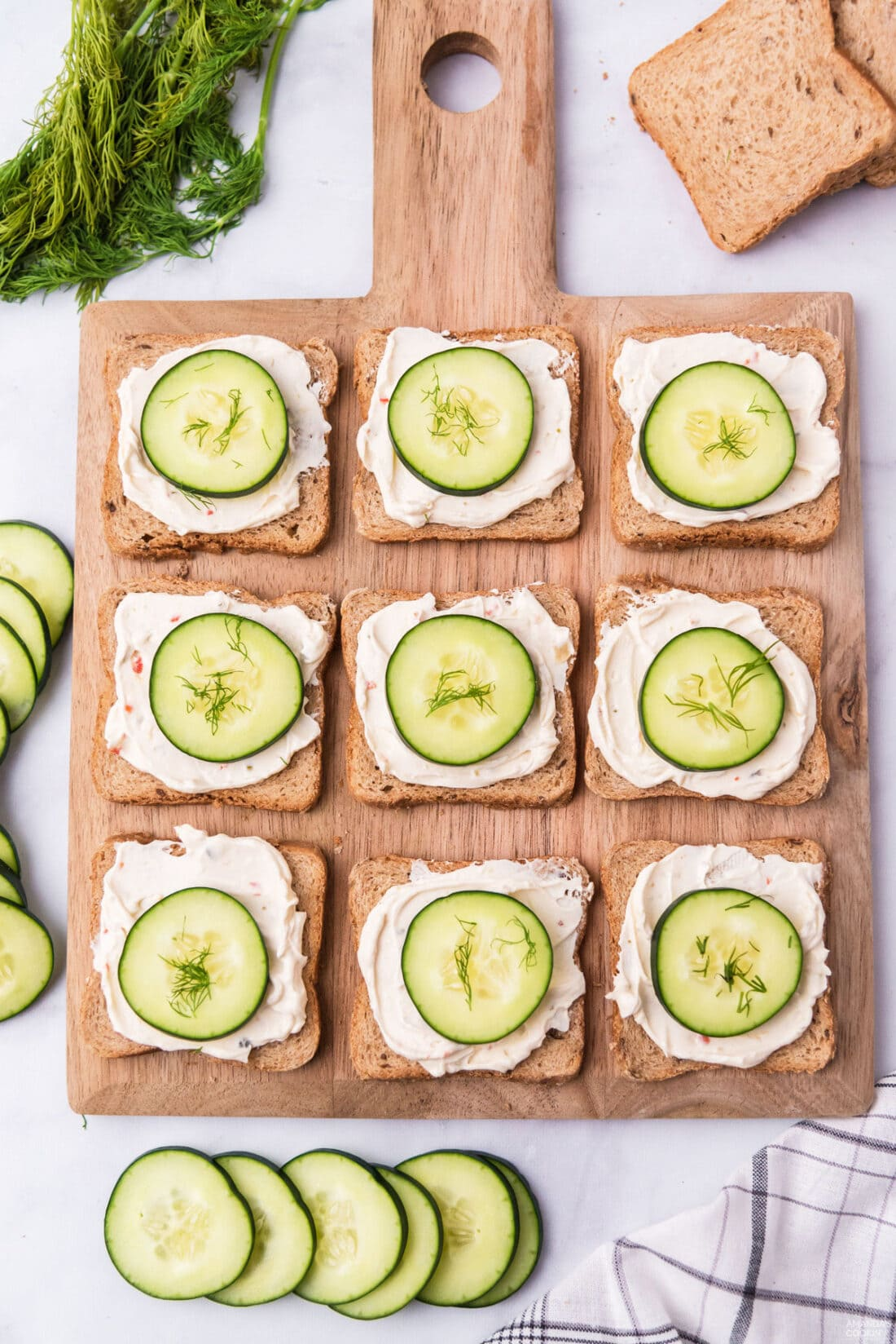 wood board with open faced cucumber sandwiches