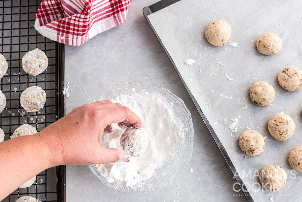 rolling cookies in powdered sugar