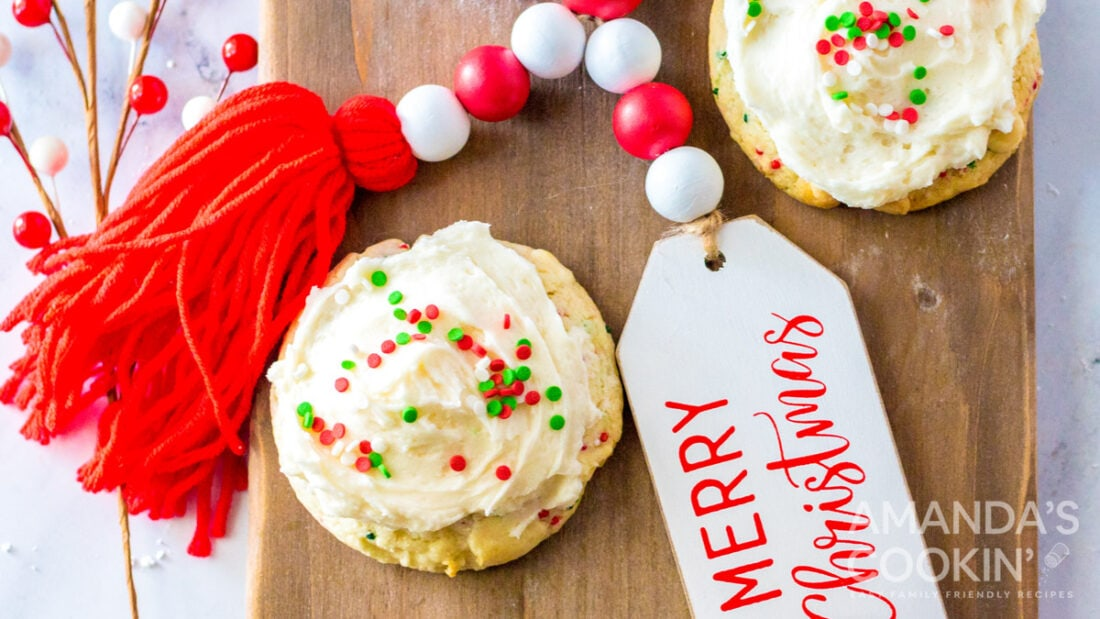 cake mix cookies with christmas sprinkles and frosting on cutting board
