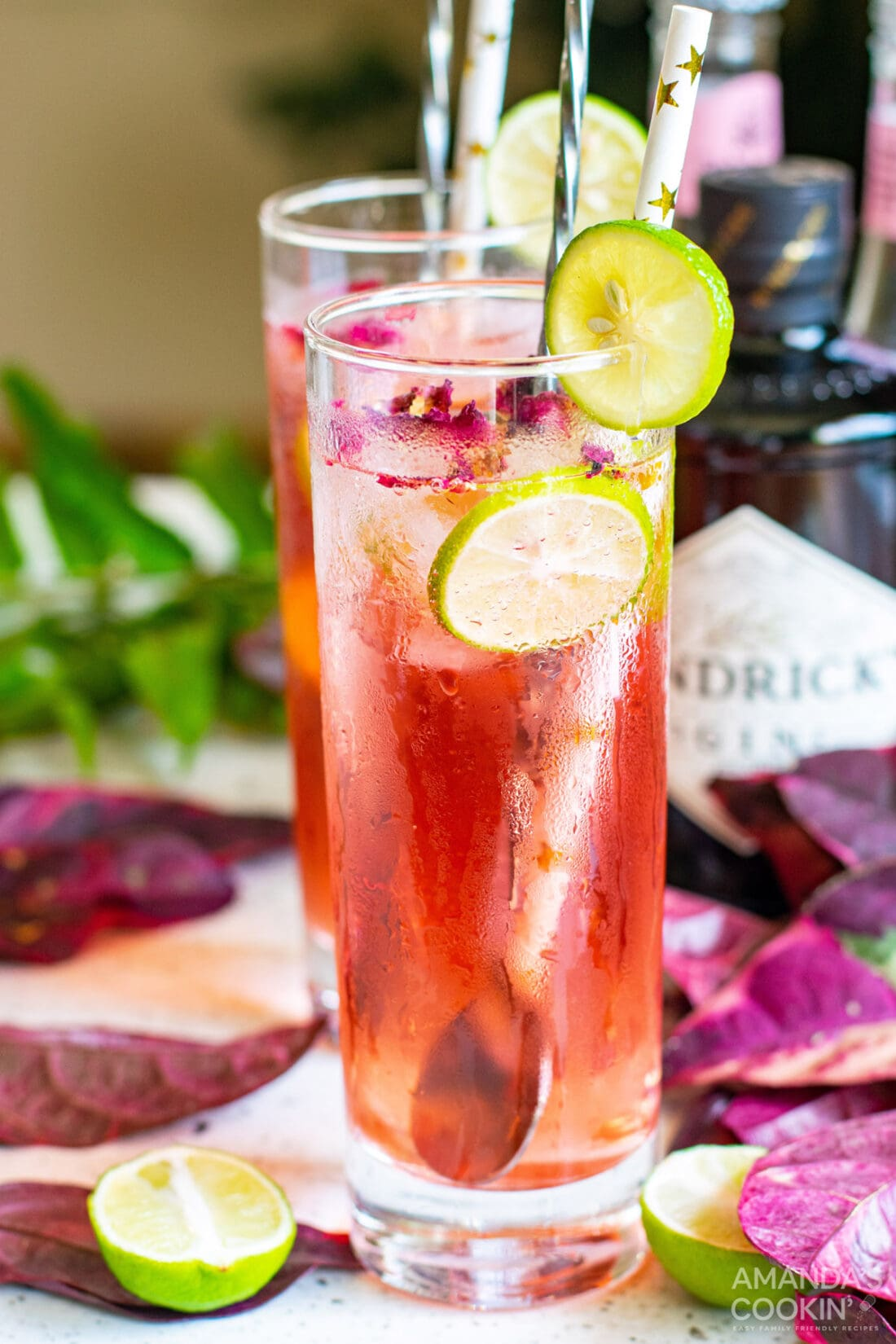 Pink Gin & Tonic with lime wedge and paper straw