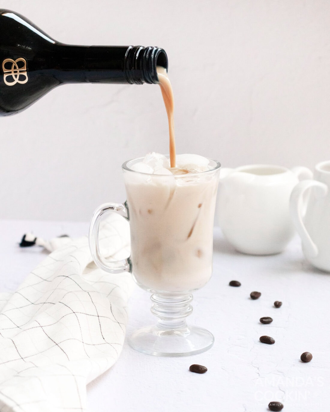 pouring baileys into a white russian
