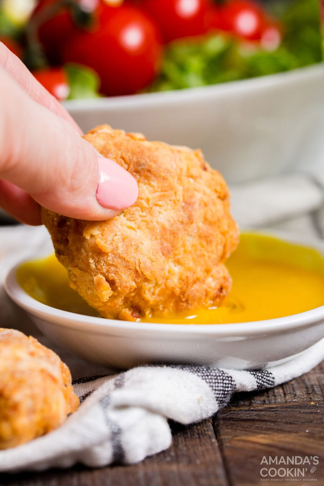 dipping chicken nugget into mustard