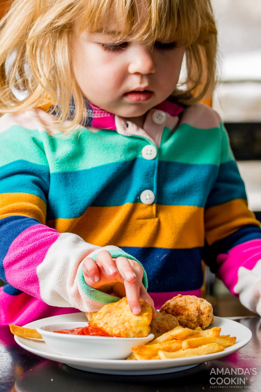 little girl dipping an air fryer chicken nugget