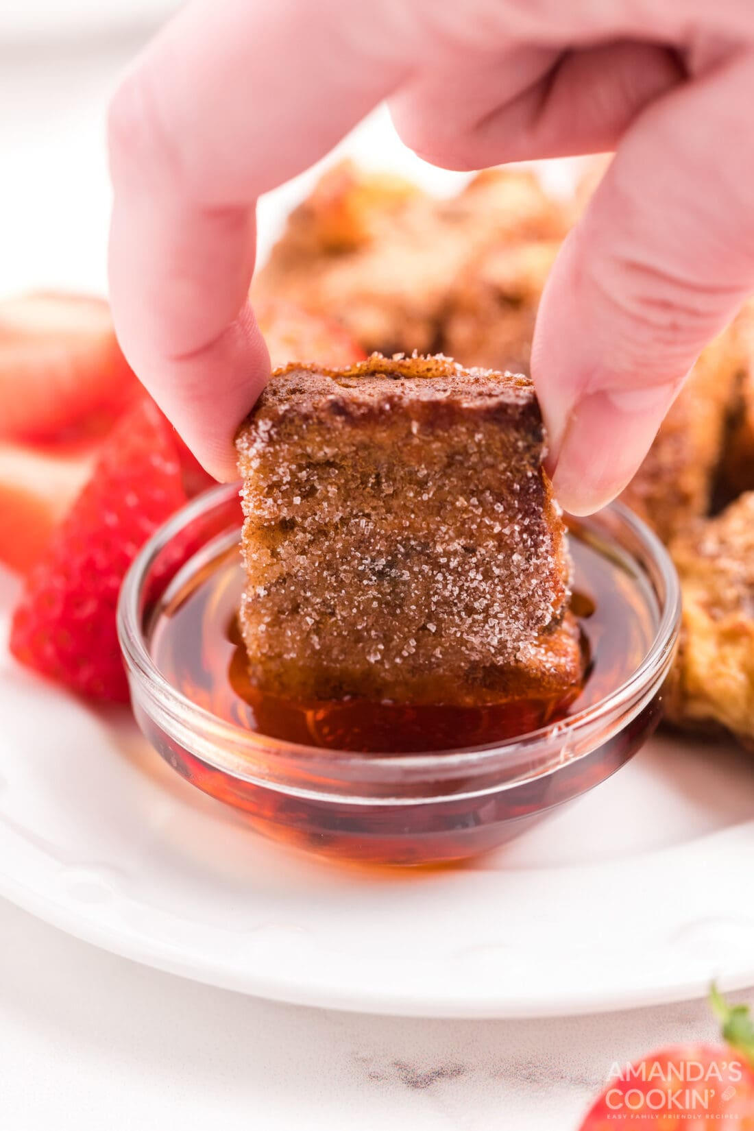 dipping a french toast stick in syrup