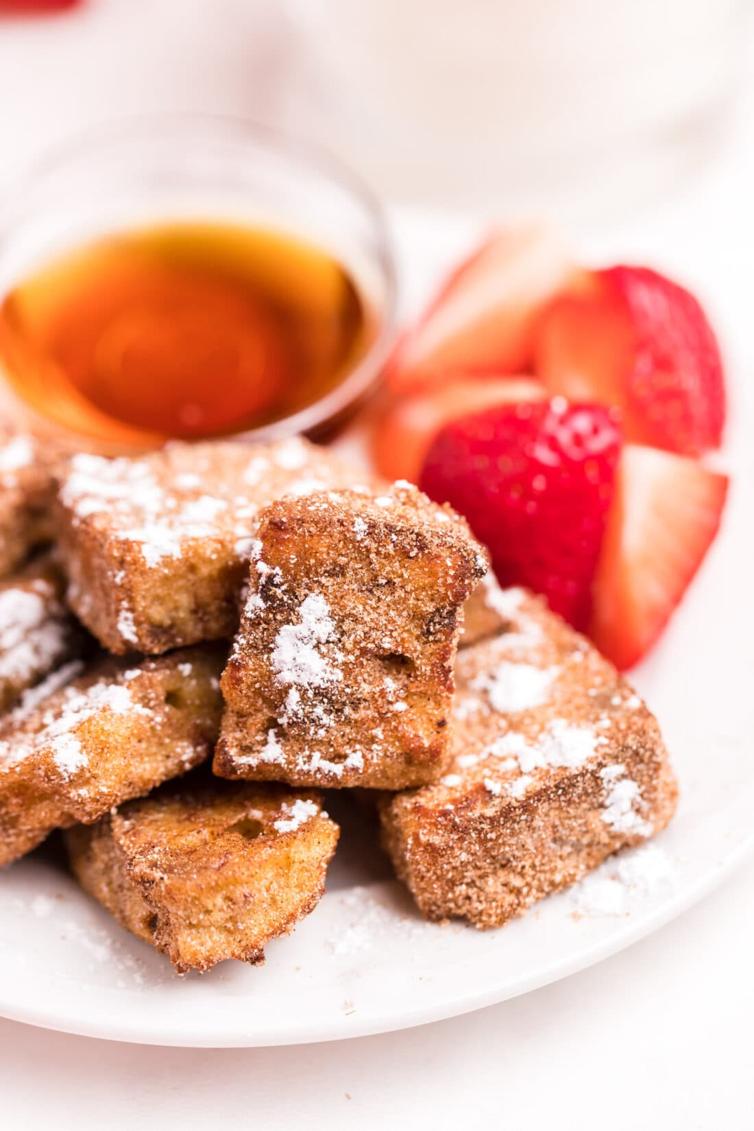 plate of Air Fryer French Toast Bites with strawberries on the side