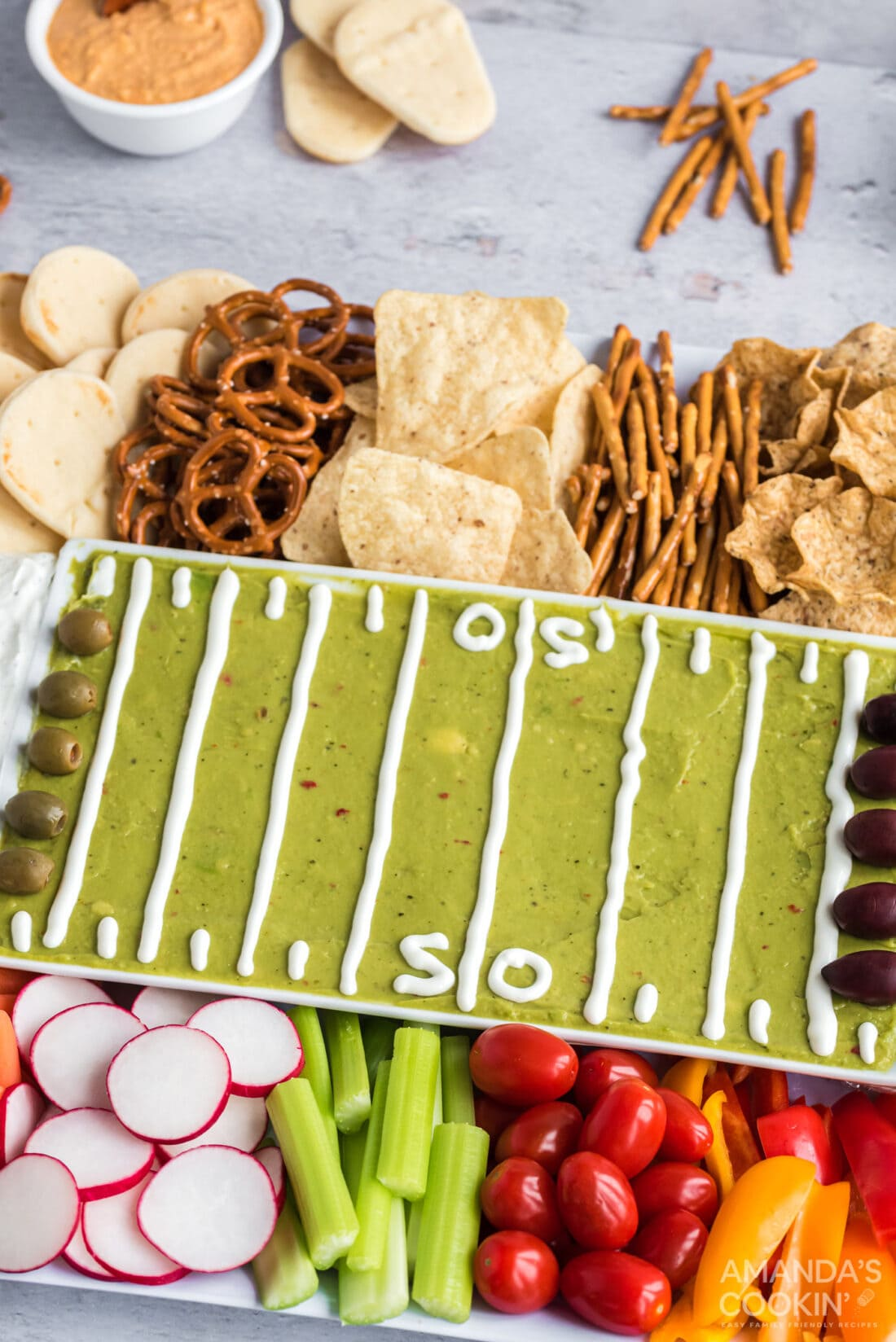 football party tray with guac, veggies, and crackers