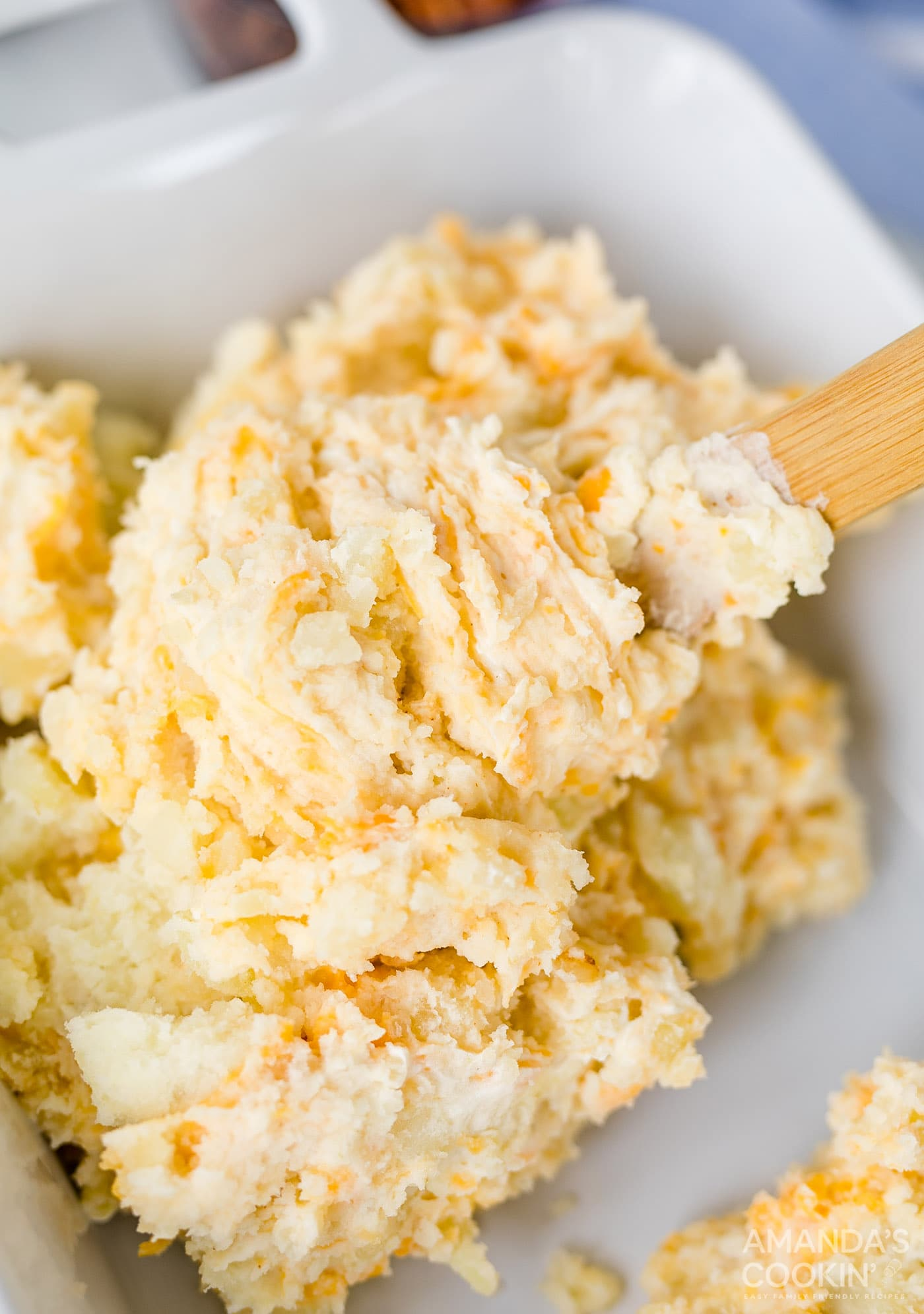 scooping mashed potatoes into a casserole dish