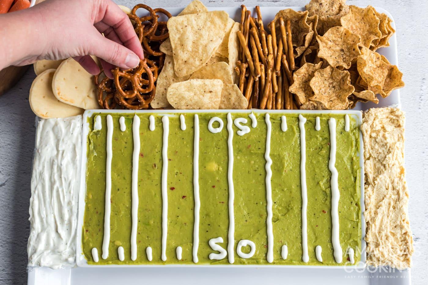 hand grabbing a pretzel on football party tray