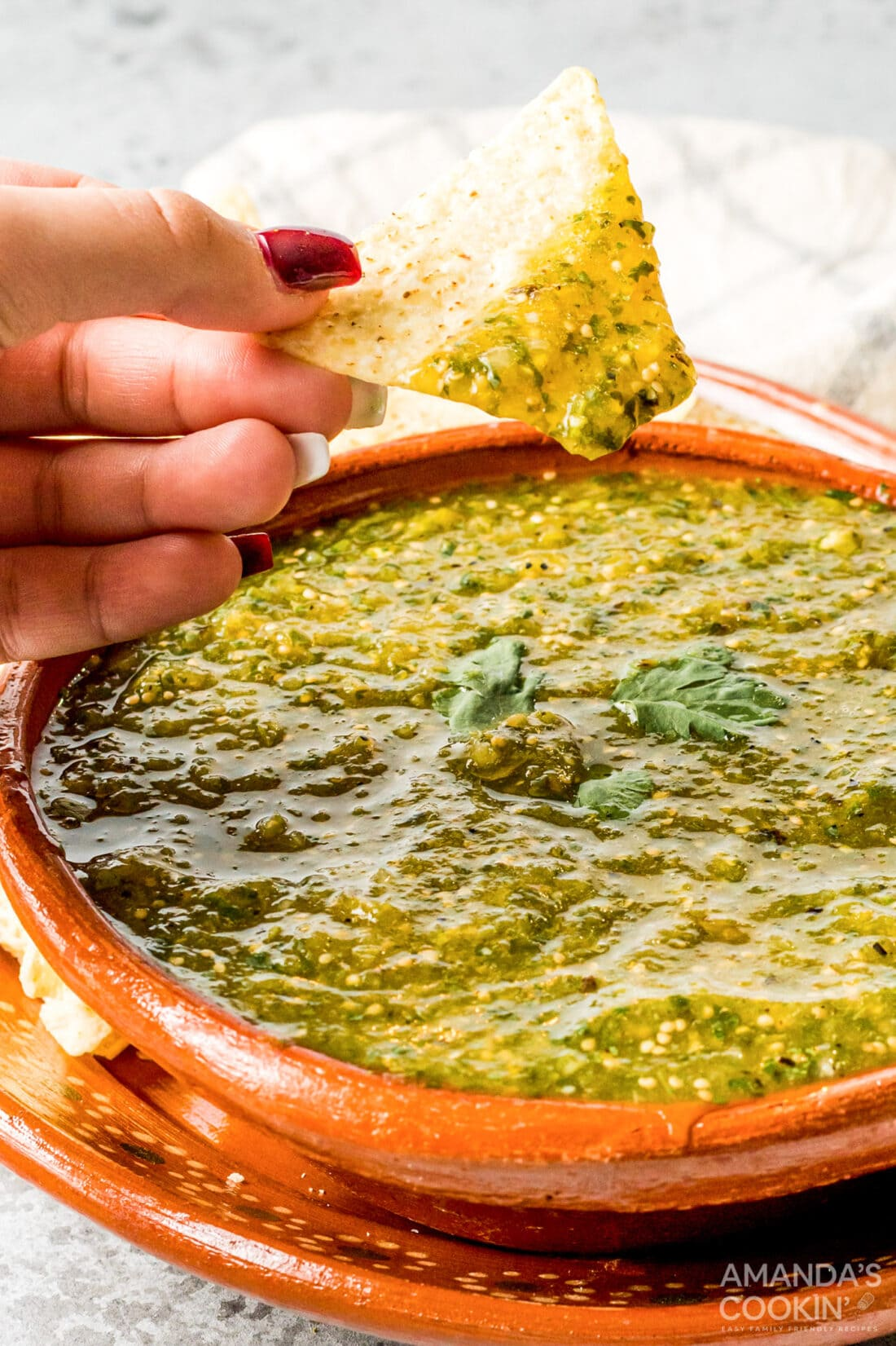 woman's hand scooping green salsa with a tortilla chip