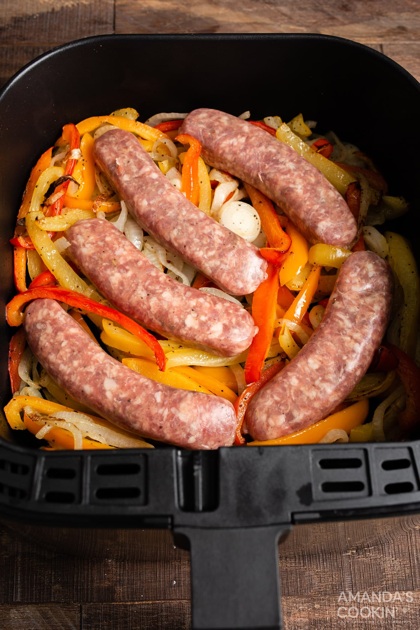 sausage and peppers in an air fryer basket