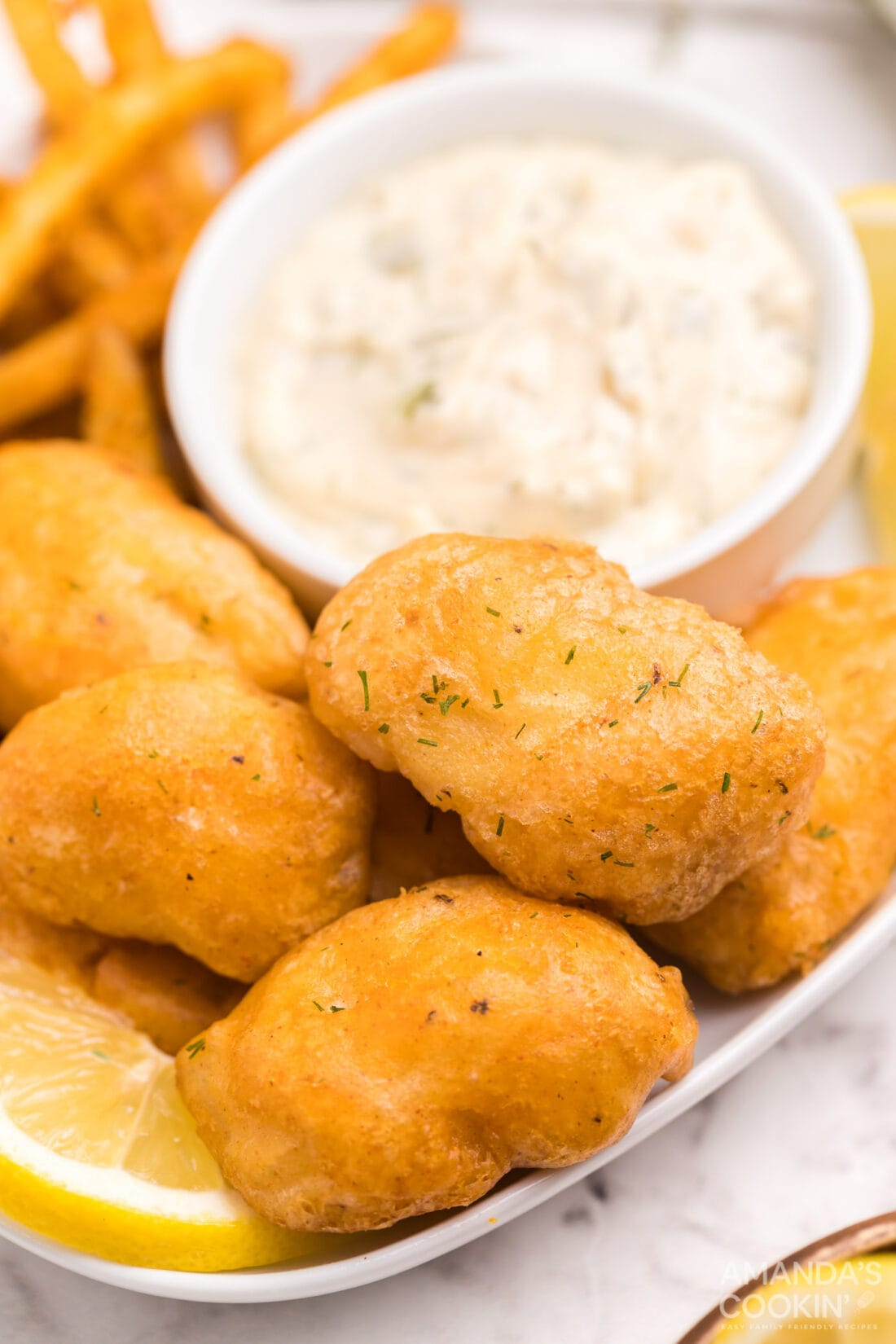 battered fish nuggets on a plate with tartar sauce