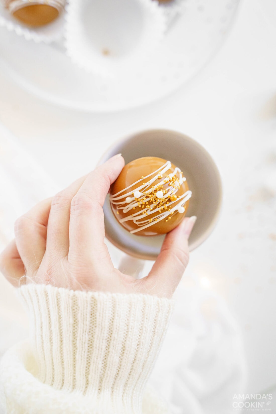 woman placing hot cocoa bomb in mug