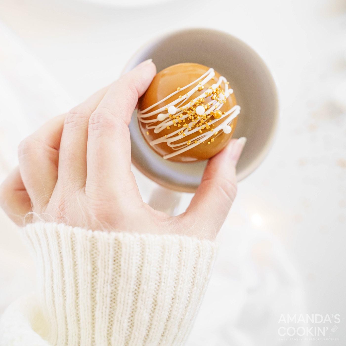 placing a hot cocoa bomb into a mug