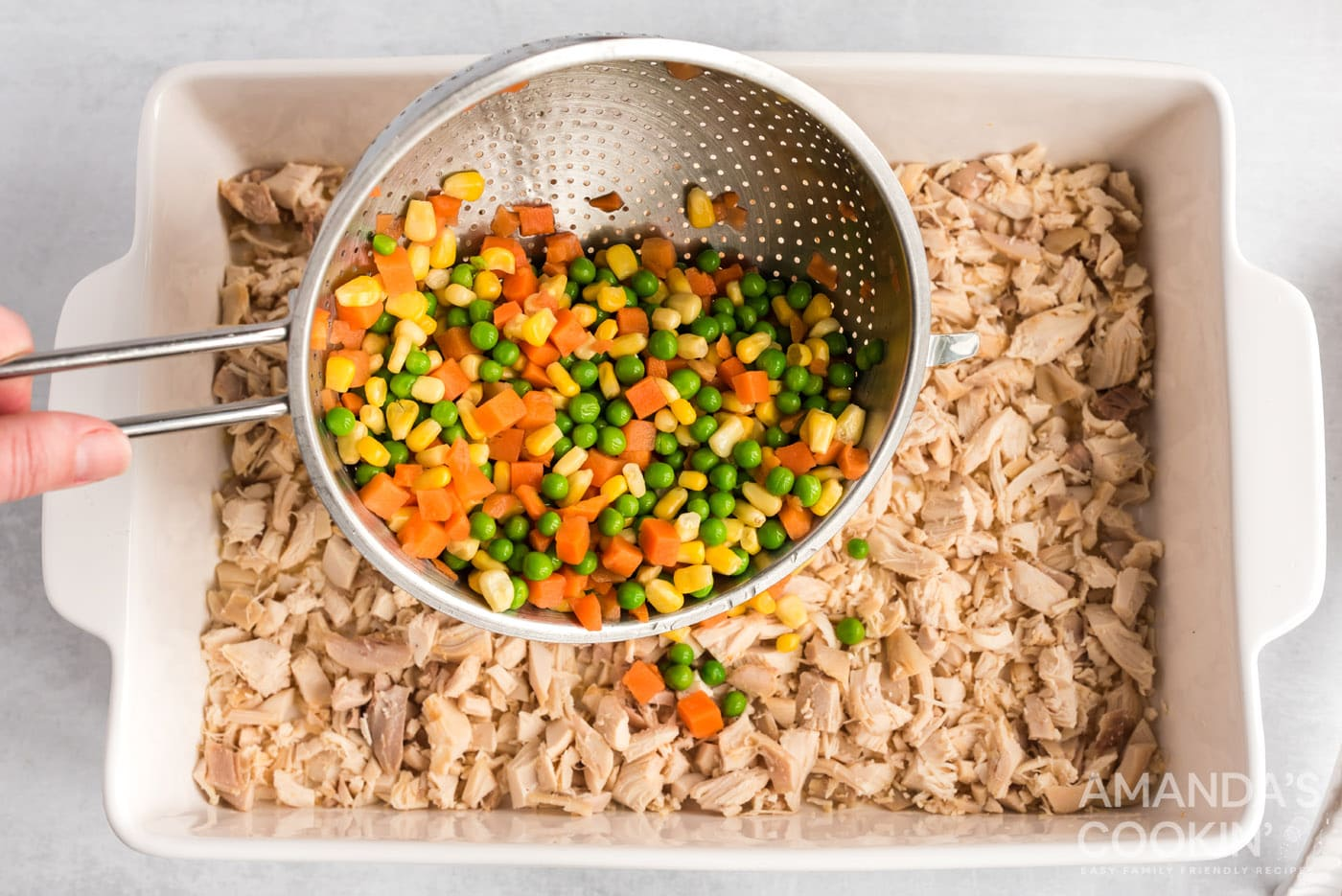 pouring frozen veggies over chicken in a pan