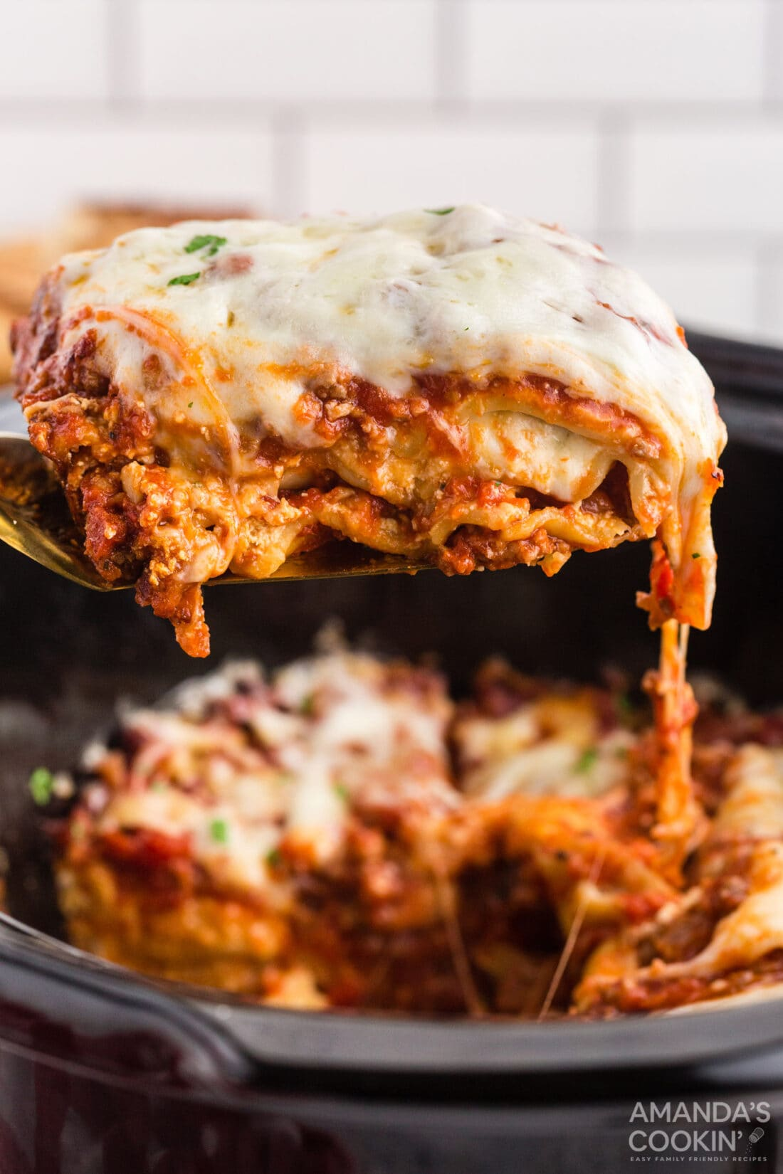 spatula lifting lasagna from a crockpot