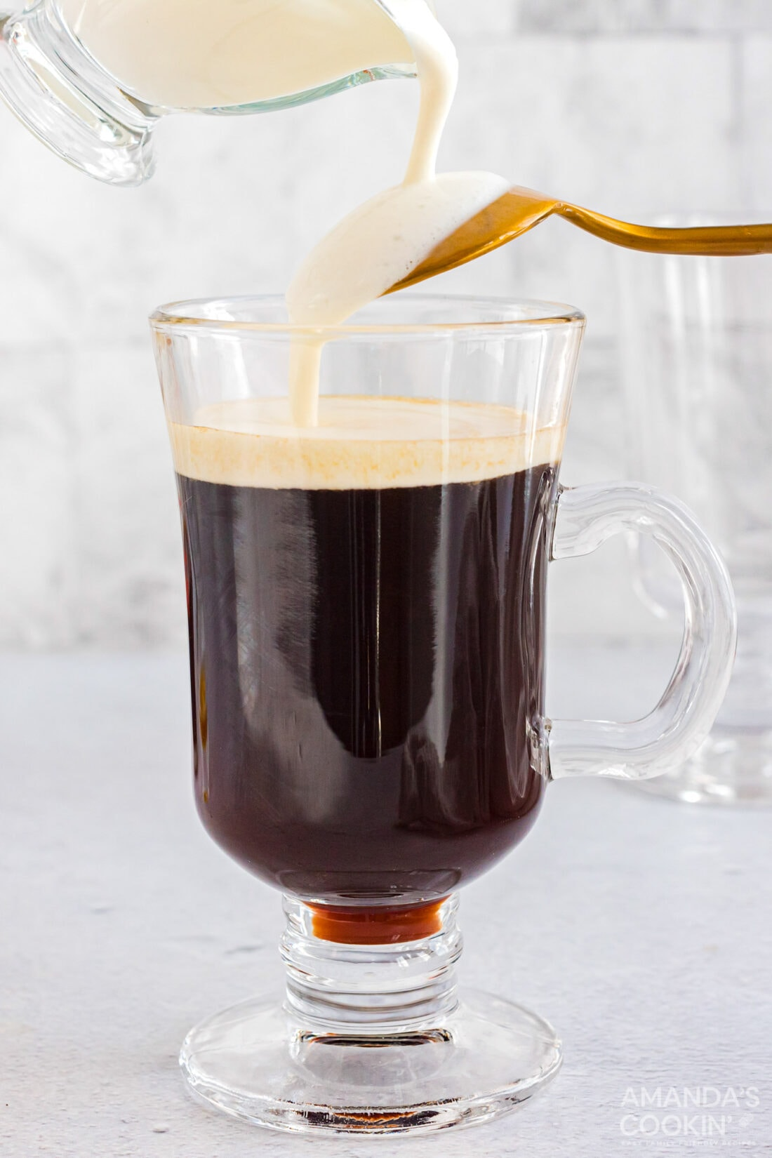 pouring cream over back of spoon into Irish coffee