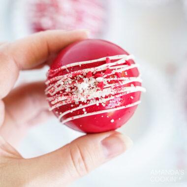 woman holding red velvet hot cocoa bomb