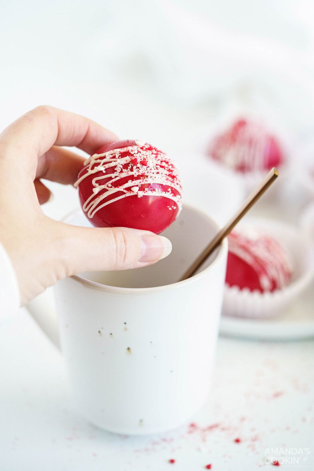 woman holding red velvet cocoa bomb over mug