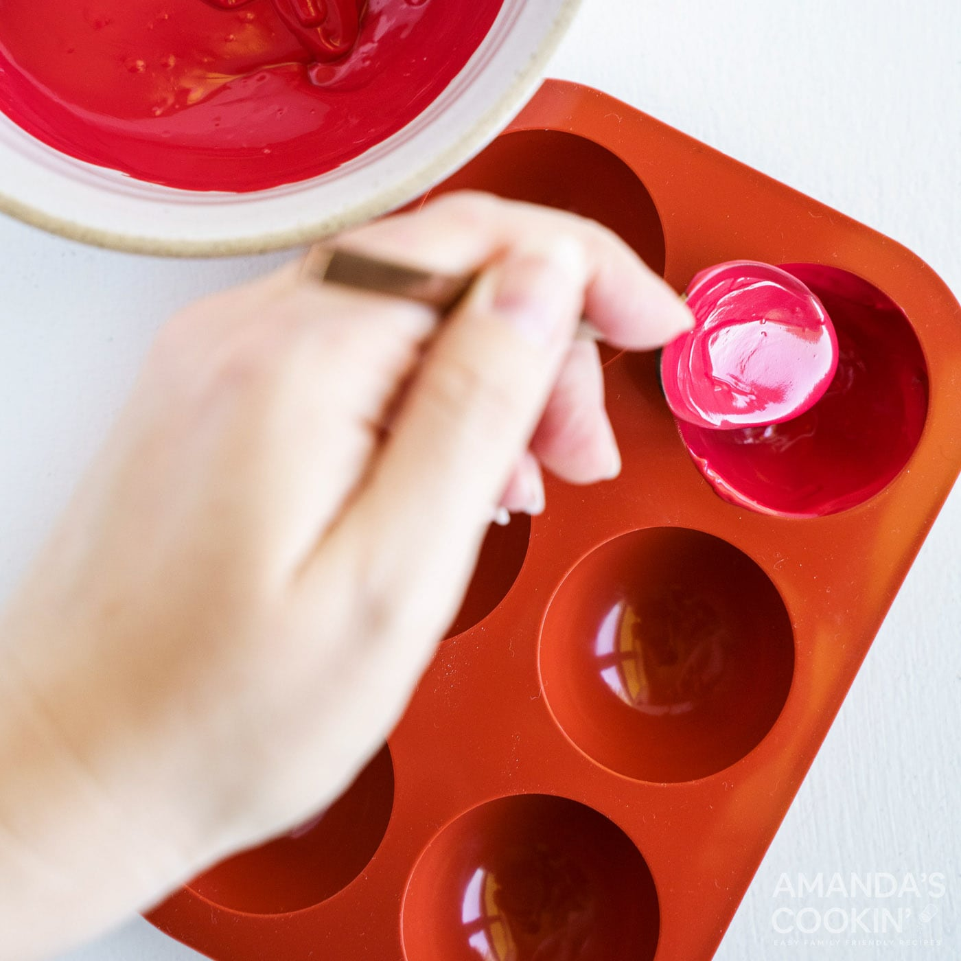 spooning melted red candy into cocoa bomb molds