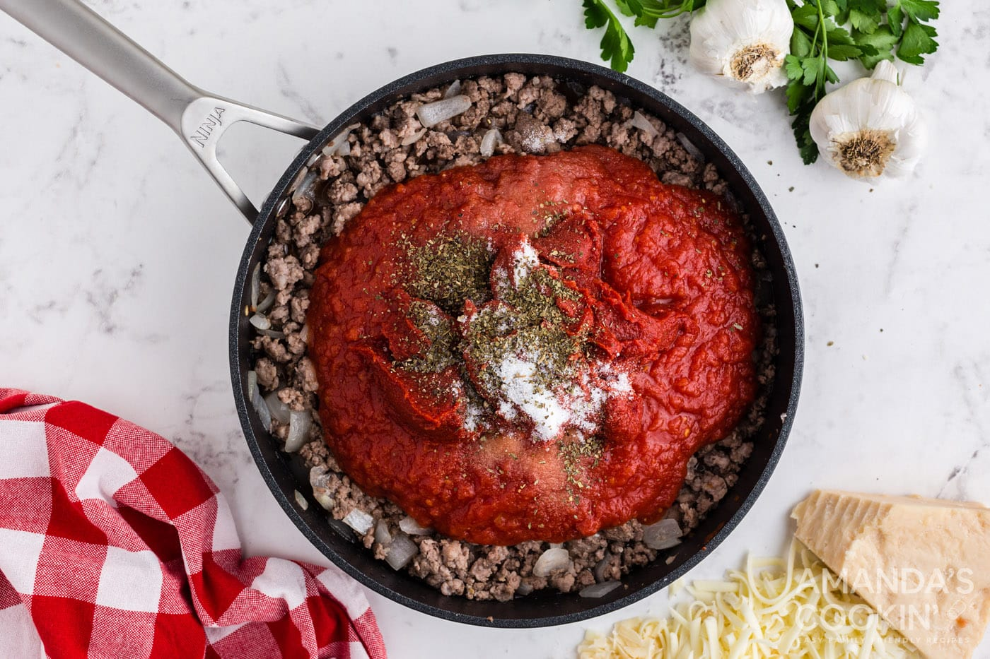 tomato sauce on top of cooked meat in a skillet