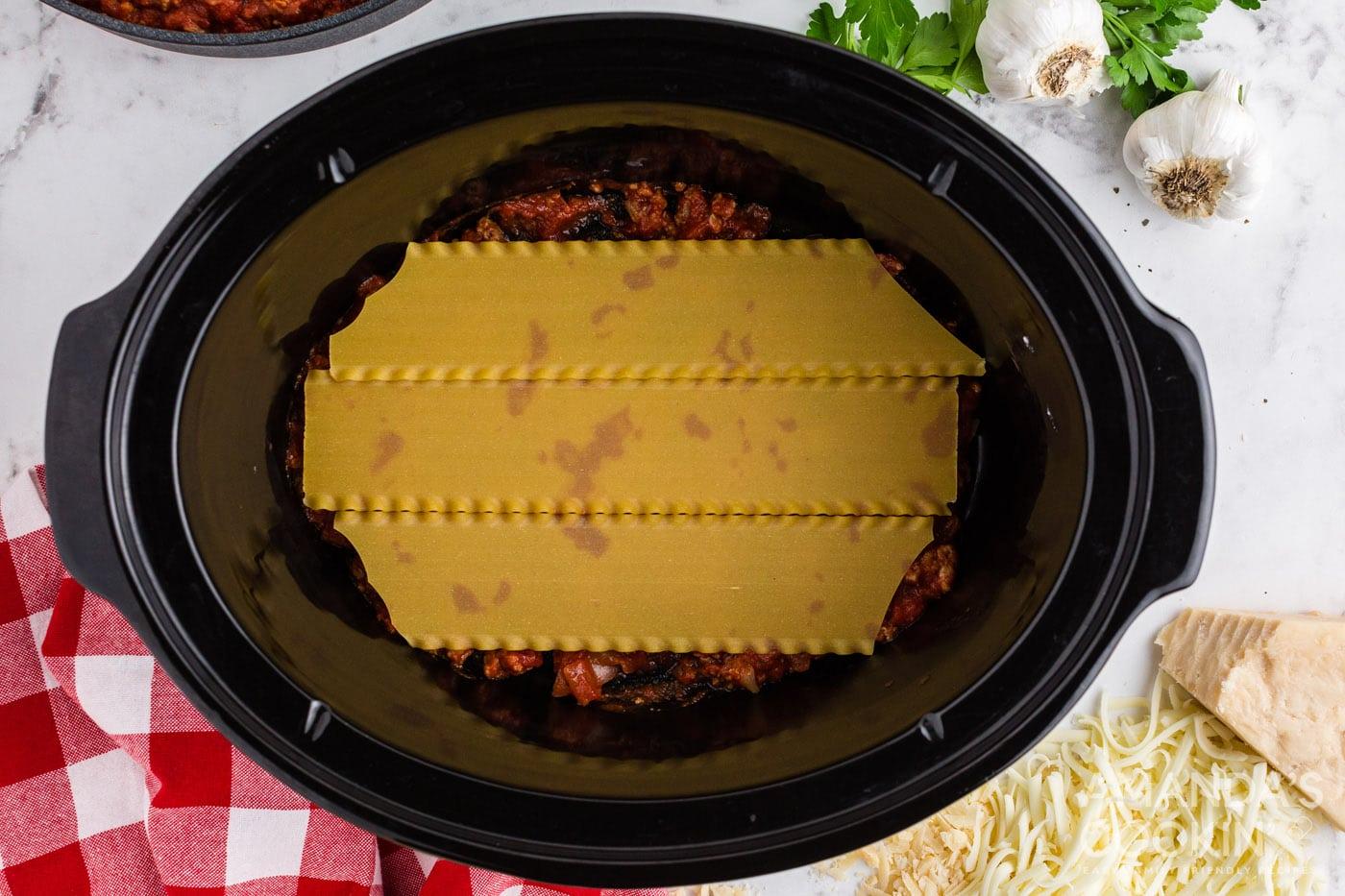 lasagna noodles on top of meat sauce in crockpot