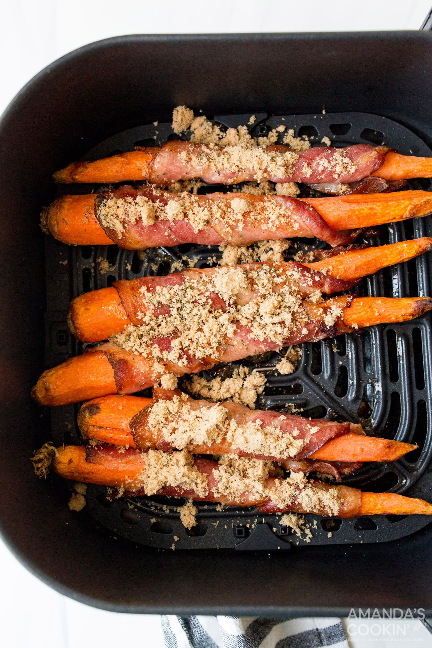 brown sugar sprinkled on bacon wrapped carrots in an air fryer