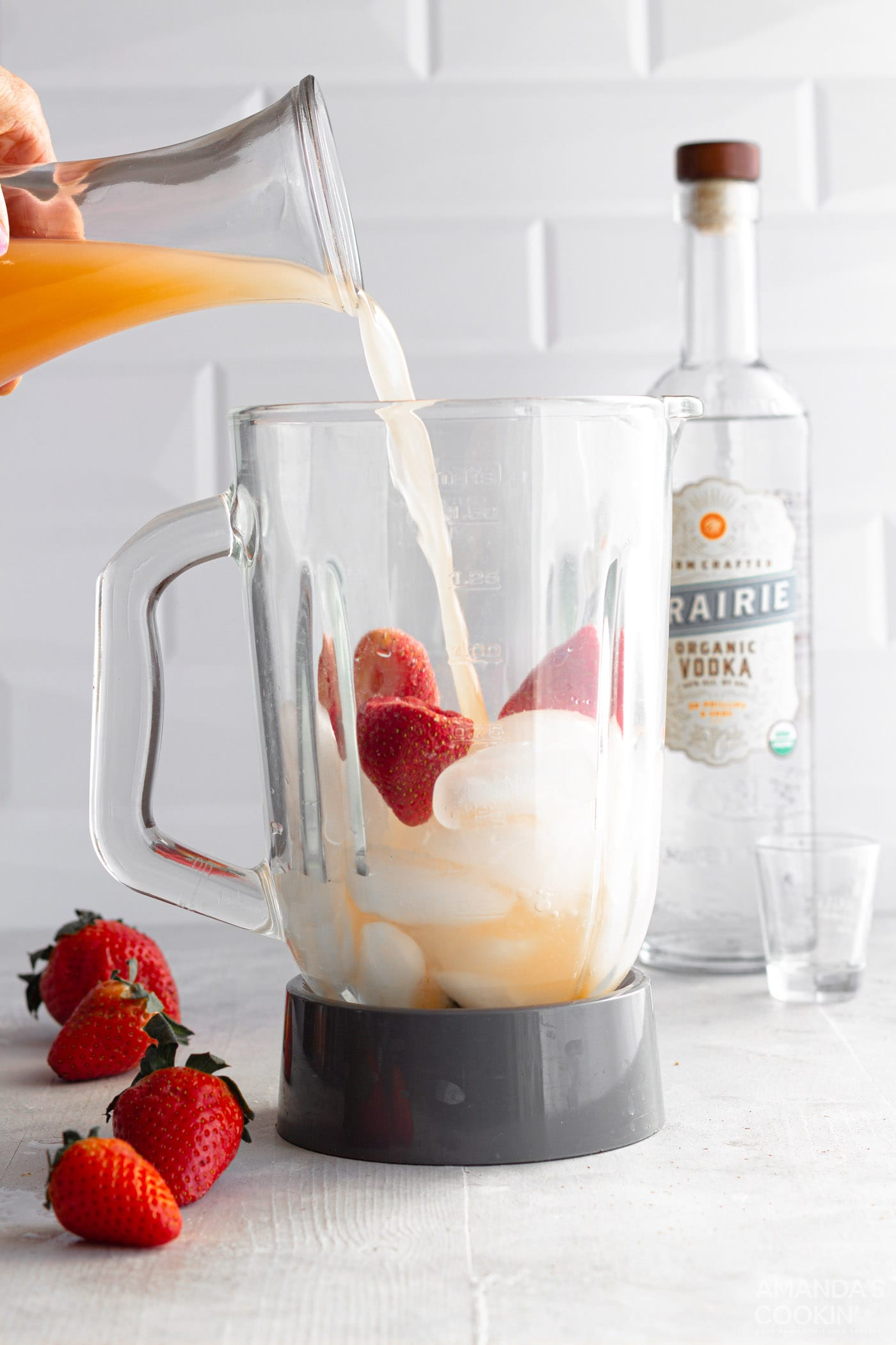 strawberries, ice, grapefruit juice, and vodka in a blender