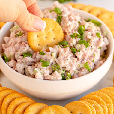 dipping cracker in a bowl of ham salad
